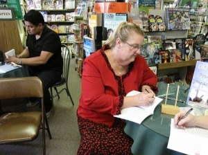 Edward Gonzales and Donna Le signing books for customers