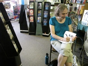 Maria Veres signing book for customer